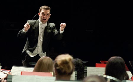 Adam Hilkert '08 conducts the George Mason University Symphonic Band. (Photo from George Mason University)